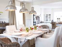 gorgeous cottage dining room with white x base dining table surrounded by white slipcover side chairs and wicker captain chairs