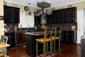 these cabinets were typical oak cabinets that you may have in your home now they have been transformed into a beautiful contemporary black distressed