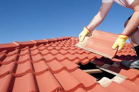 broken roof tile is pried out so that a new replacement can be slipped in beneath