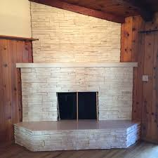 this white stone veneer fireplace with a marble granite outer hearth will warm up the