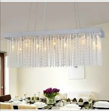 rectangle dining room crystal chandelier over dining table with flower centerpiece in crystal vase and white cutlery