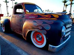 studebaker pickup truck ratrod with rusty metal finish under flat black flame that are pinstriped in red all sitting on red steel wheels wrapped in wide