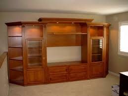 large brown wooden wall unit entertainment center with racks and glass doors on the floor