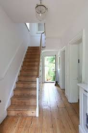 natural pine flooring and staircase and white walls with clear gl light fixture