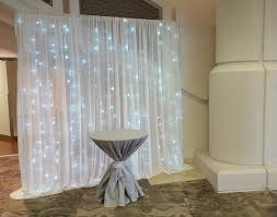 white satin and chiffon backdrop with led lights behind for the cake table