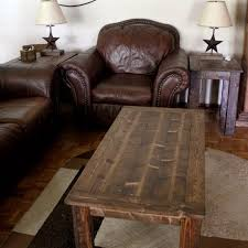 a wooden coffee table in a living room with leather furniture ana white