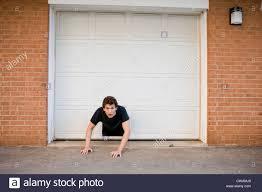 Decorating garage man door images : Young man crawling through hole in garage door Stock Photo ...