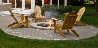 sophisticated small backyard patio garden ideas using round open fire pit combine wooden lounge chairs on concrete paving floor