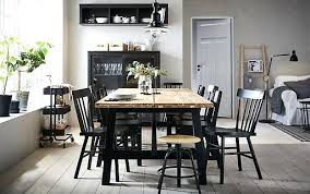 ikea dining room the acacia table is positioned in centre of a beige and black chairs uk