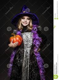 portrait of little in witch costume with pumpkin character