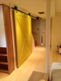 mive yellow barn door on a horseshoe barn door hardware to give privacy to the bat