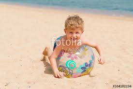 Beach ball in ocean Fun Smiley Little Blond Kid Is Playing With The Inflatable Translucent Beach Ball On The Sandy Sea Ocean State Job Lot Smiley Little Blond Kid Is Playing With The Inflatable Translucent
