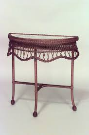 American Victorian natural wicker half round small console table with  filigree apron and decorated top under glass (matching mirror)