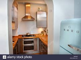 Fitted Kitchen A Small Fitted Kitchen With A Smeg Fridge Uk Stock Photo Royalty