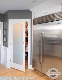 A frosted pantry door adds a stylish element to this gray and white ...