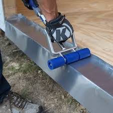 exterior door threshold install. pressing sill into place at the bottom of door frame with a roller. exterior threshold install