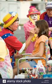 clowns do face painting to raise money at american cancer society s relay for life charity event in ocala florida usa