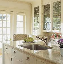 glass building kitchen cabinets. in this soft cream #kitchen the upper cabinets showcase decorative stained glass. love glass building kitchen s