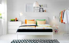 A white bedroom with a large bed made with bedlinen in orange and green, a