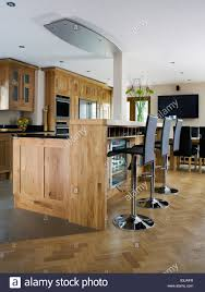 Black Stools At Breakfast Bar In Modern Country Kitchen With