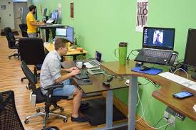 standing desk office. people working at desks along wall. standing desk office h