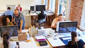 wide angle view busy design office. wide angle view of busy design office with workers at desks a