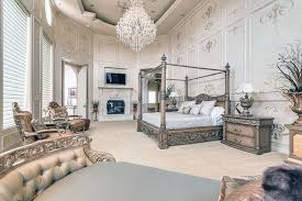 luxury traditional master bedroom with gilded bed frame high ceilings and crystal chandelier