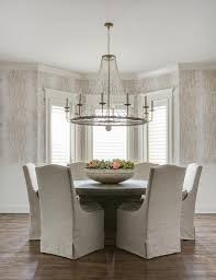 gray linen slipcovered dining chairs with round wood table