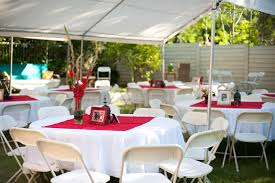 backyard party decorations mixed with round tables also white table clothes and white folding chairs on green grass yard and striking red flowers plus