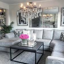 mirrors mirror frames and a crystal chandelier spruce up the grey space