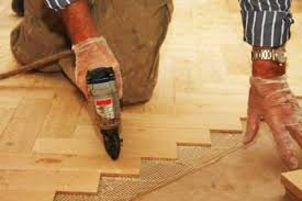 A Contractor Laying Down A Hardwood Floor In A Herring Bone Pattern.