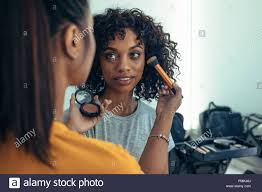 makeup artist applying foundation to a model using a brush professional makeup artist preparing a model for a photo shoot