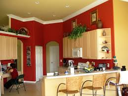 kitchen red wall theme and cream wooden kitchen cabinet connected by white bar top