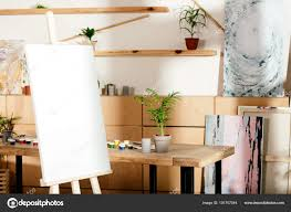 interior artist studio easel table painting supplies potted plant stock photo