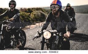 smiling friends wearing decorative gles three men wearing open face crash helmets and goggles riding cafe racer motorcycles along rural road