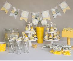 white table with glasses also yellow white cup cakes on the two layer tray also hanging love word placed on the gray wall
