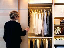 woman opening a sliding door and looking inside a wardrobe ikea pax white sliding door wardrobe