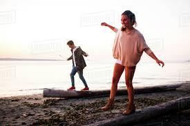 Walking Logs Caucasian Couple Walking On Logs On Beach Stock Photo Dissolve