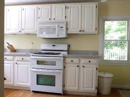 magnificent white melamine kitchen cabinets with gray granite countertop and white microwave oven on yellow kitchen