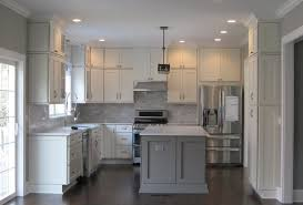 kitchen has white shaker cabinets on the perimeter gray marble backsplash soft gray island