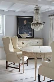 english country decor in a serene white cote style room with swedish antiques round table wing chairs and empire style crystal chandelier