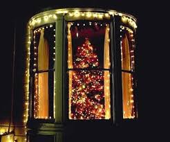Candle Burning In The Window Of A House With Christmas Tree In The Christmas Tree In Window