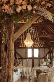 rustic wedding lighting. crystal wedding chandelier with a fairy light canopy at the beautiful loseley park tithe barn lighting by oakwood events ltd flowers rustic