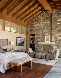 imposing stone wall adds to the dramatic ambiance of the bedroom design gregory carmichael