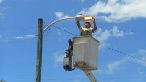 an electrical foreman installs a new 2700k led streetlight in lake worth florida concerned