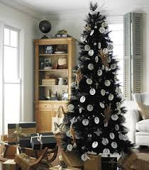 Black Christmas tree decorating with handmade white ornaments and gift  boxes in black and brown colors