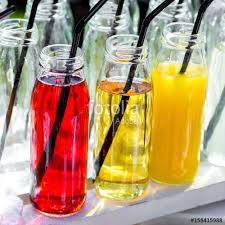 colorful cocktails or juices shots with straws in small glass bottles