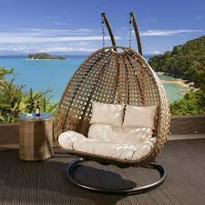 dark brown rattan two person hanging chair with cream cushion covers