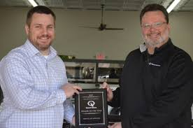 bob wallace appliance co owner chris haygood left accepts a plaque from john keys of o rourke s the distributor of sd queen appliances in the