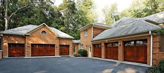 a red brick home contains two sets of three wooden garage doors that sit at a